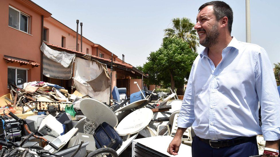 Matteo Salvini stands by a pile of rubbish as he tours the Mineo migrant centre, 9 July 2019