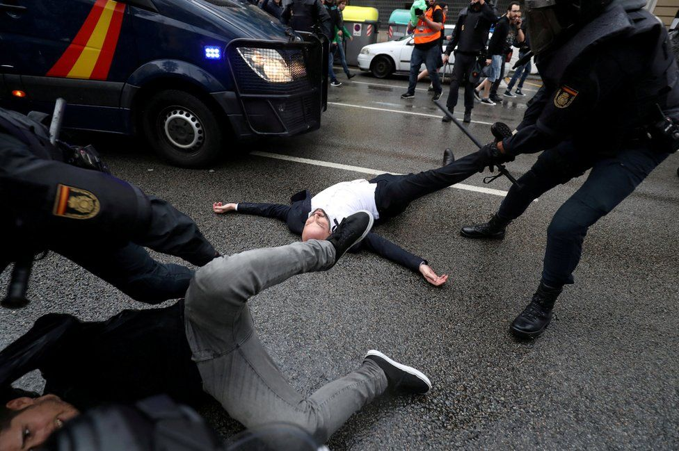 Spanish Civil Guard officers remove demonstrators outside a polling station for the banned independence referendum.