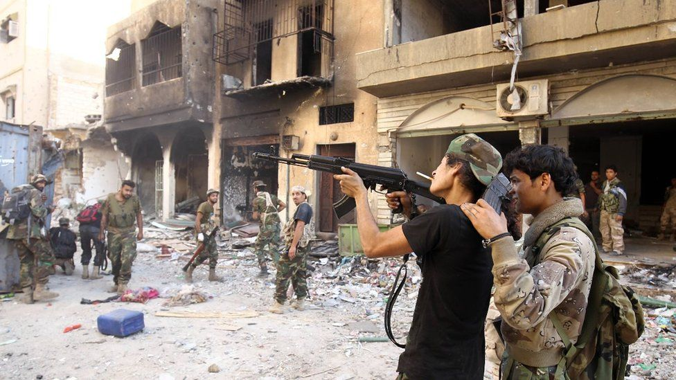 Members of the self-styled Libyan National Army, loyal to the country's east strongman Khalifa Haftar, practice firing a Kalashnikov assault rifle as they rest following clashes with militants in Benghazi's central Akhribish district on November 9, 2017.