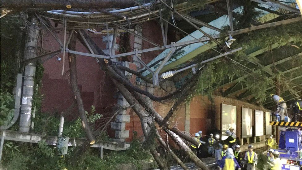 Workers remove fallen branches from Tokyo's Yotsuya station, 1 October 2018