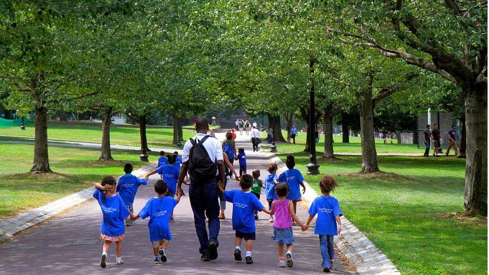 A daycare class walking in a public park in Boston