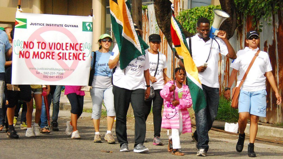 """SASOD activists on a march holding banners demanding """"no more violence, no more silence"""""""