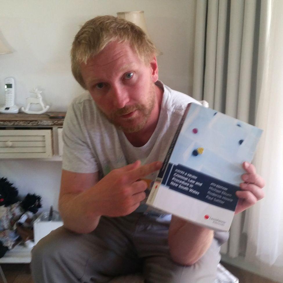 Luke Brett Moore with law book