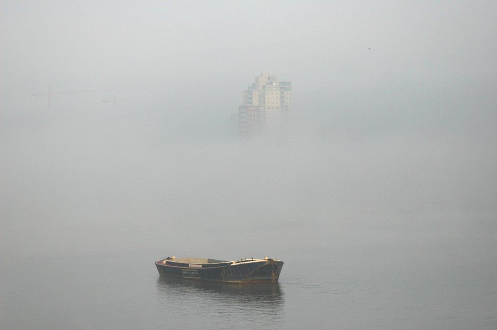 A small boat and top of a block of flats are the only things visible through mist