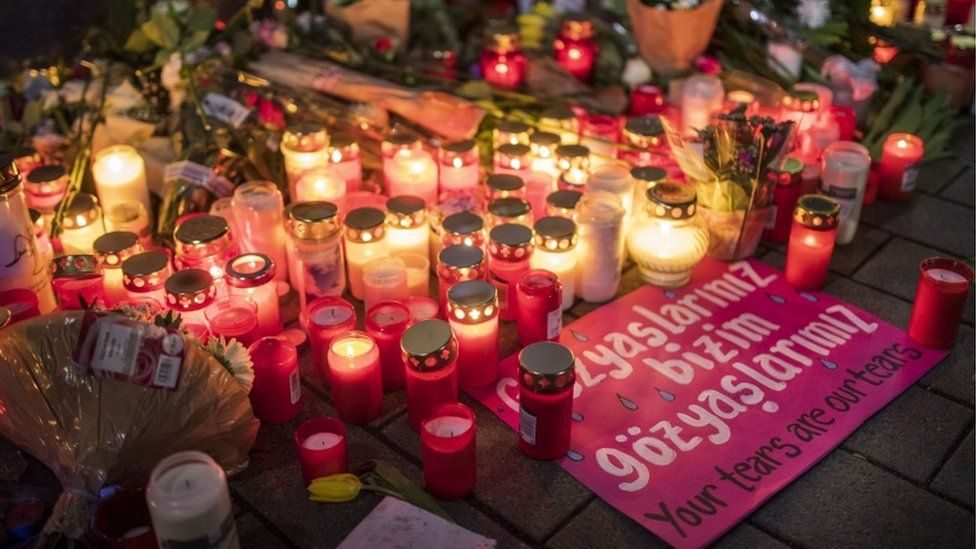 """Candles, flowers and a sign with the slogan """"Your tears are our tears"""" pictured near the scene of one of the shootings in Hanau, Germany"""