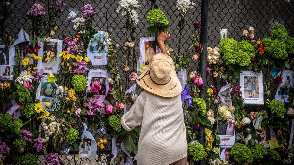 A woman adds flowers to a memorial outside Champlain Tower