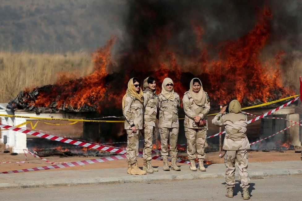 Members of the anti-narcotics force pose for a picture as drugs are burned during a ceremony in Islamabad, Pakistan
