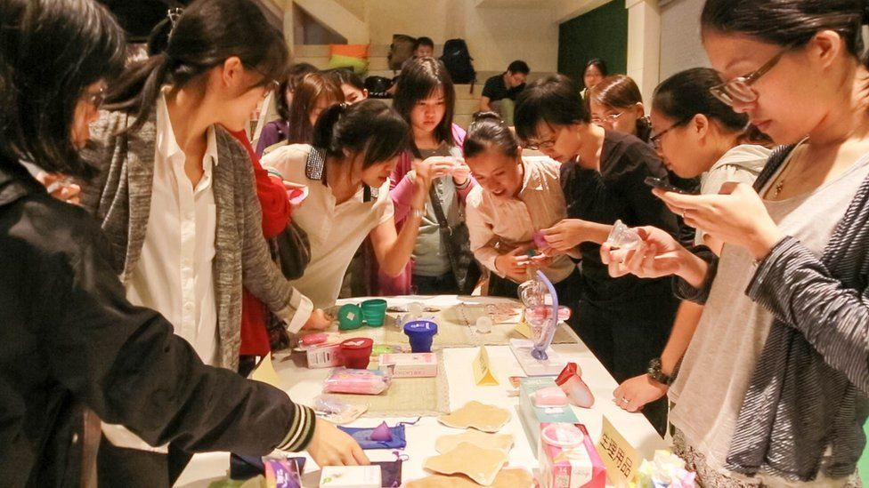 Women look at different menstrual cups with enthusiasm during a promotional event in Taipei