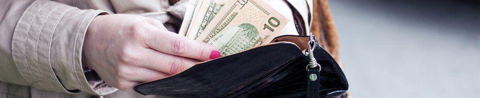 Woman putting dollars in purse