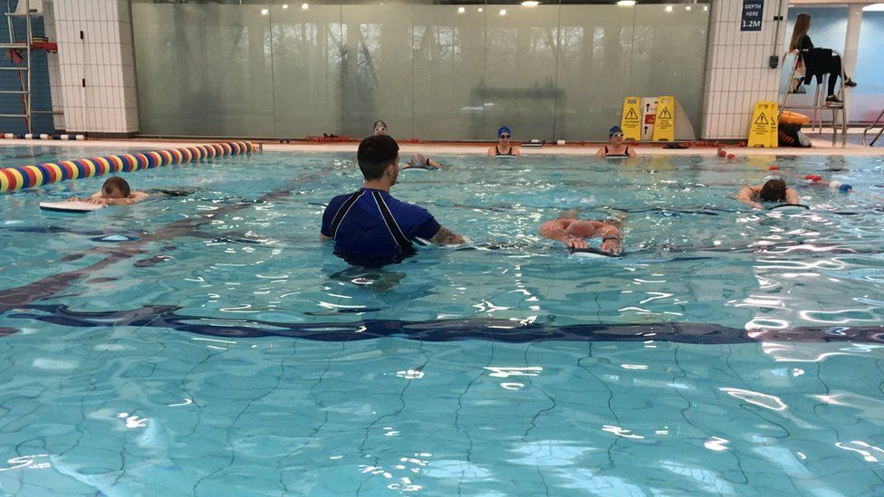 Adults learning to swim as part of a swimming lesson
