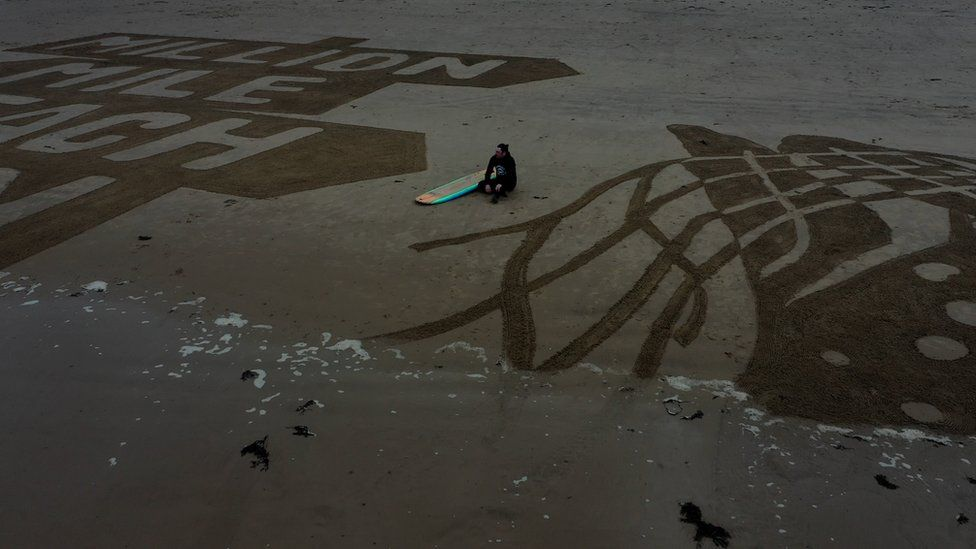 Surfer sitting on Cayton Bay beach between the sand drawing