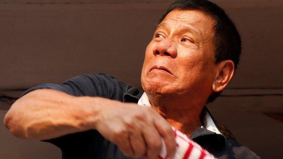 "Presidential candidate Rodrigo ""Digong"" Duterte throws election souvenir shirts to his supporters during election campaigning in Malabon, Metro Manila"