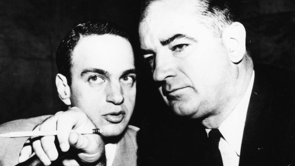 Senator Joseph McCarthy and attorney Ray Cohn in 1954 lean heads together