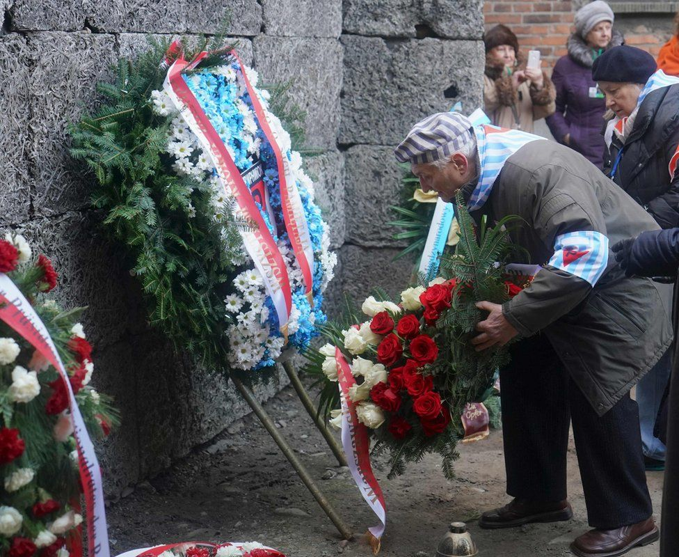 Survivors and other guests attend a wreath-laying ceremony