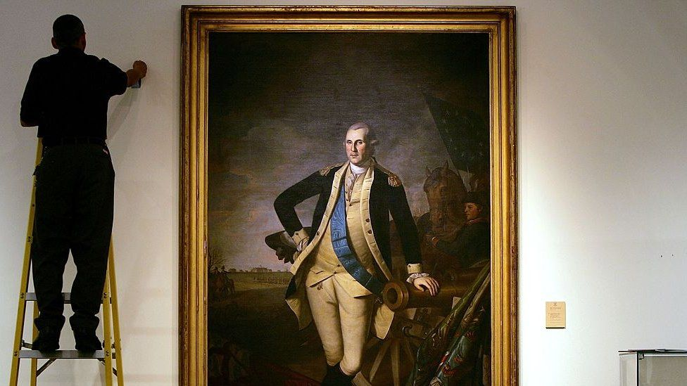 A worker uses a ladder to work near a full length portrait of former U.S. President George Washington, by Charles Wilson Peale, at Christie's auction house January 17, 2006