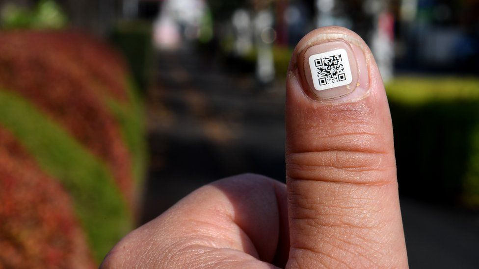 A sticker displaying a QR code is seen attached to a fingernail in the city of Iruma, a western suburb of Tokyo, 5 December 2016