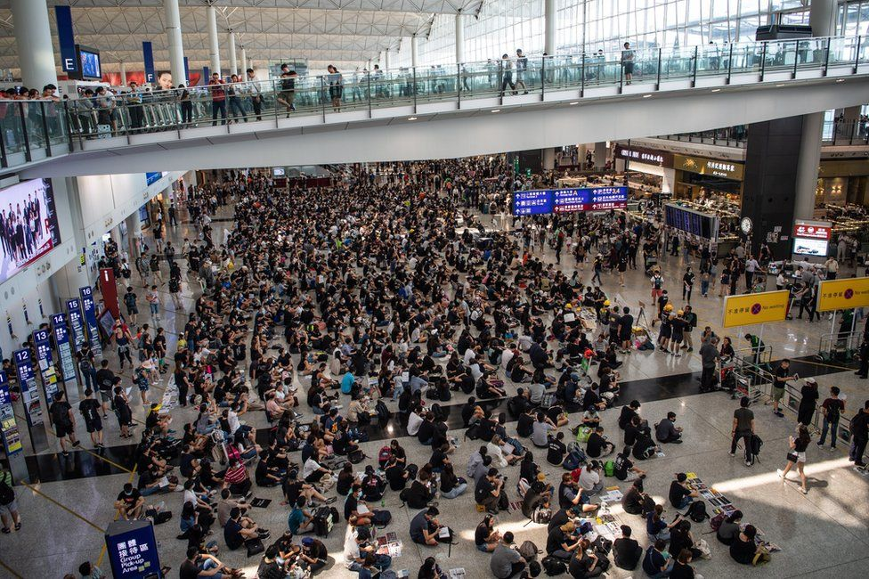 Protesters attend a sit-in against police violence in Hong Kong Chek Lap Kok International Airport