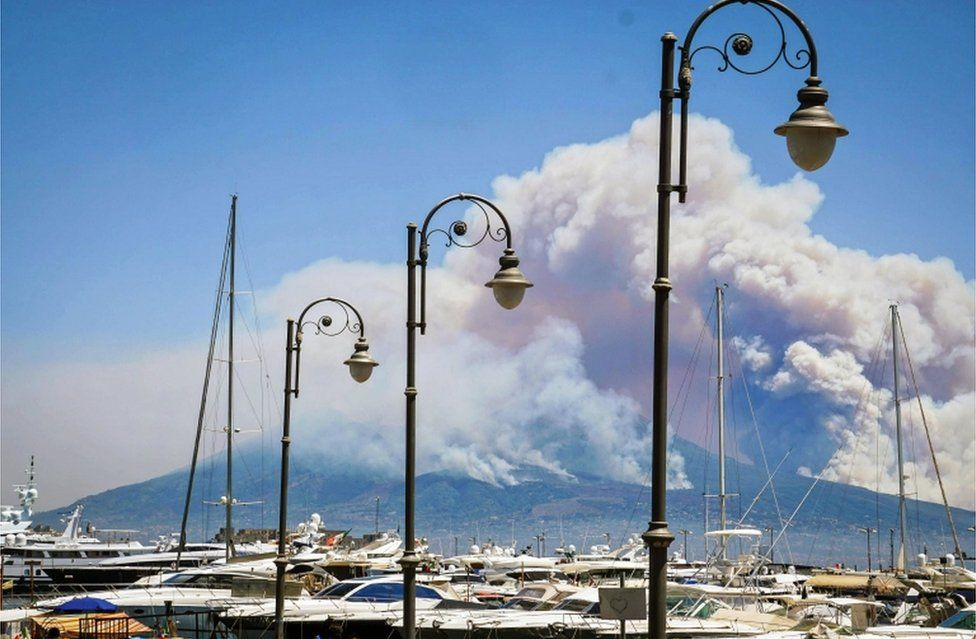 A general view over the city as smoke billows from fires around Mount Vesuvius volcano in Naples, Italy, 11 July 2017.