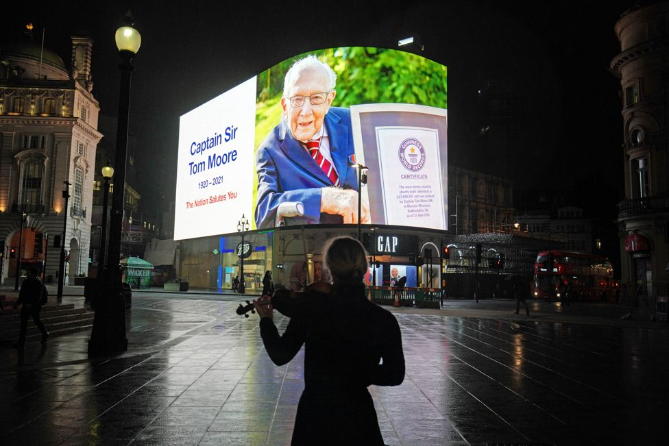 A woman plays the violin in Piccadilly Circus during a tribute to Captain Sir Tom Moore on 2 February 2021
