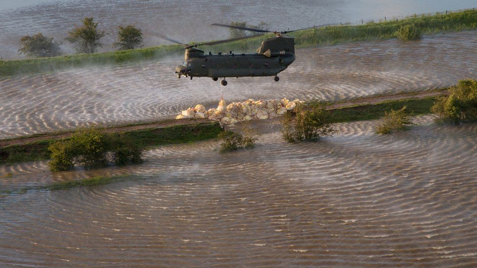 RAF Chinook helicopter dropping ballast on the breach in the River Steeping