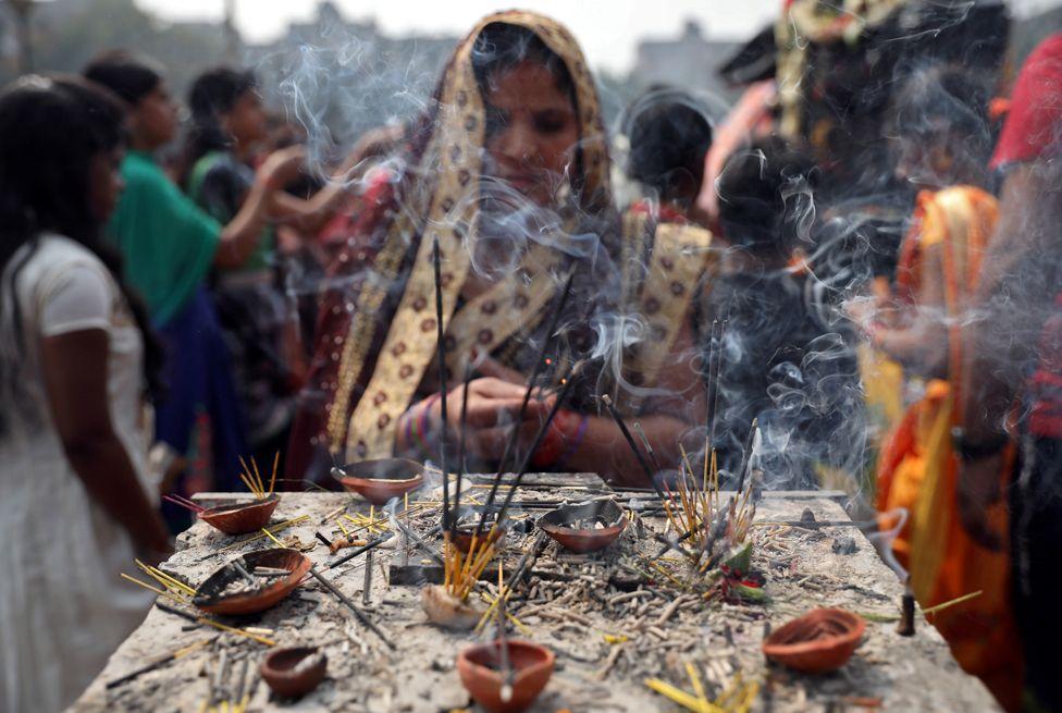 A woman burns incense sticks as she prays at a temple on the occasion of the Hindu festival of Maha Shivaratri in Kolkata, India, 21 February 2020.