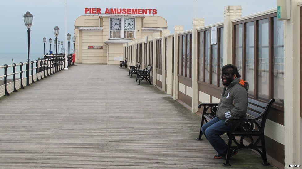Aceves sitting on a bench on Worthing Pier