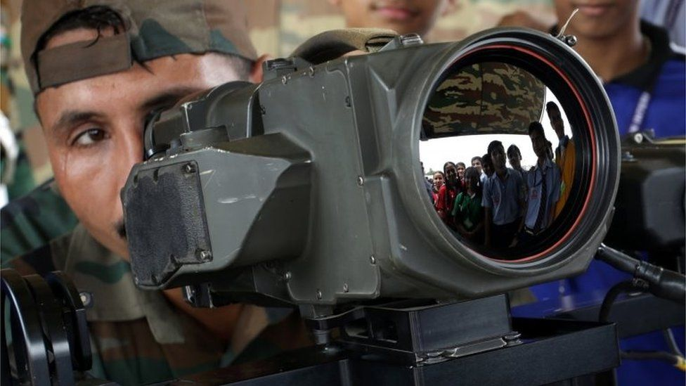 An Indian army soldier explains the function of thermal imaging device to students during a military exhibition in Jammu, the winter capital of Kashmir, India, 10 August 2018.