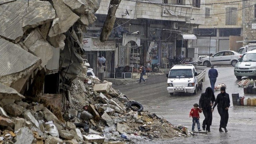 Civilians walk in the rain past a damaged building in the rebel-controlled area of Maaret al-Numan town in Idlib province, Syria October 28, 2015
