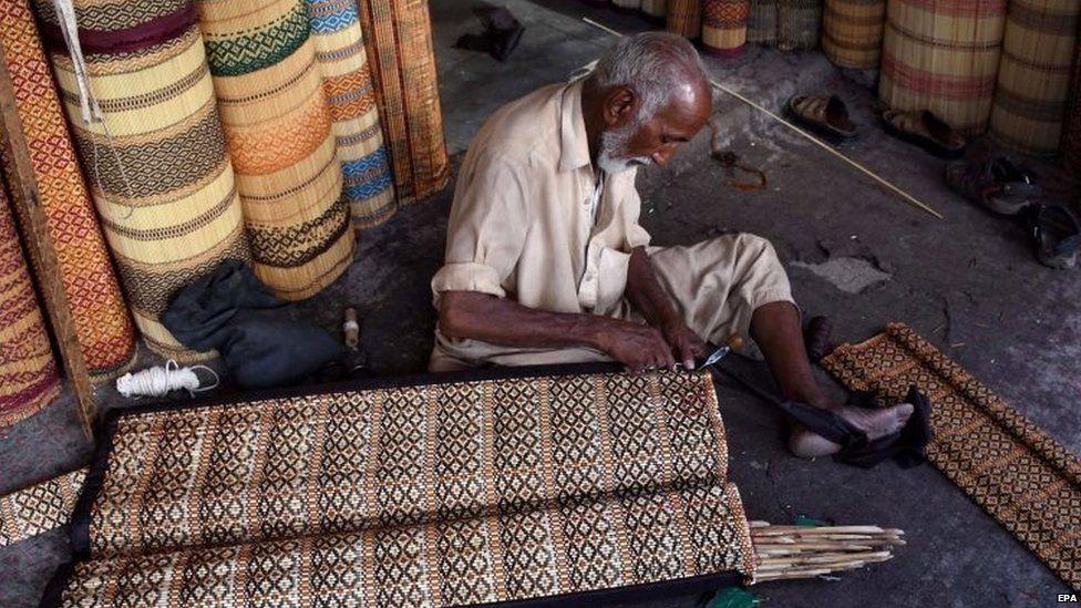 A man prepares handmade curtains in Karachi. Photo: 11 June 2015