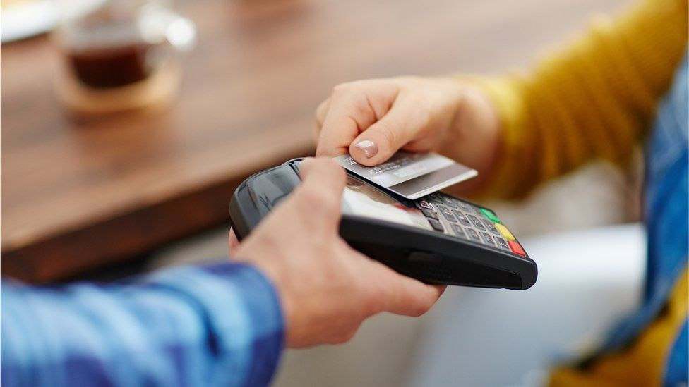 A customer pays for a coffee using a contactless payment card