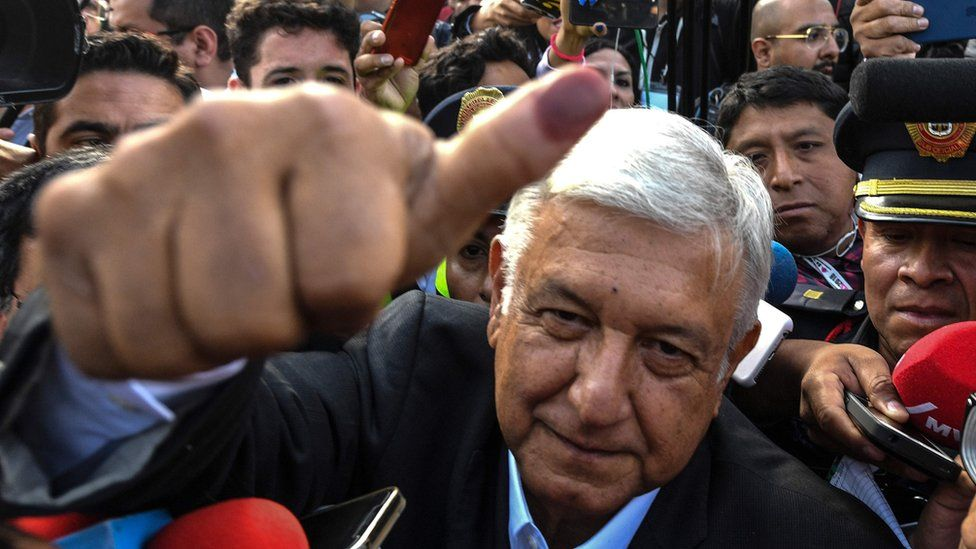 """Mexico's presidential candidate Andres Manuel Lopez Obrador for the """"Juntos haremos historia"""" party, gives his thumb up while leaving the polling station during general elections, in Mexico City, on July 1, 2018."""