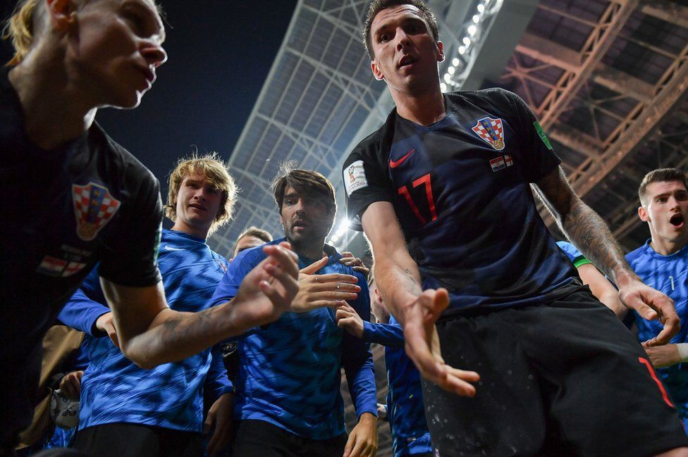 Croatia's forward Mario Mandzukic (C) offers to help AFP photographer Yuri Cortez after he fell on him with teammates while celebrating their second goal