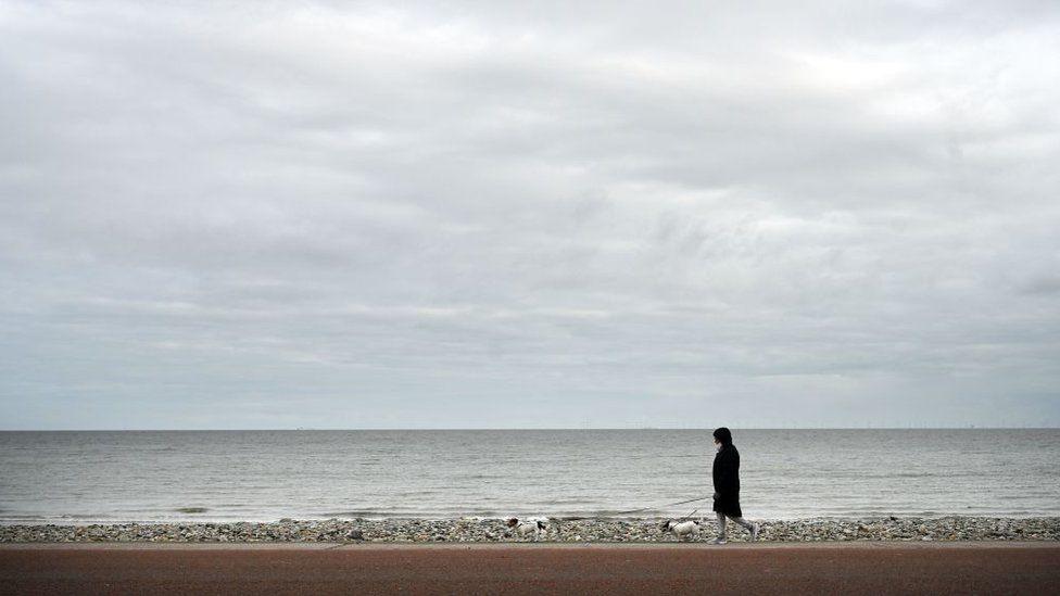 person walking along empty beach