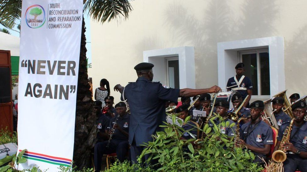 "A band playing at the launch of the TRRC next to a banner saying, ""Never again"" - October 2018"
