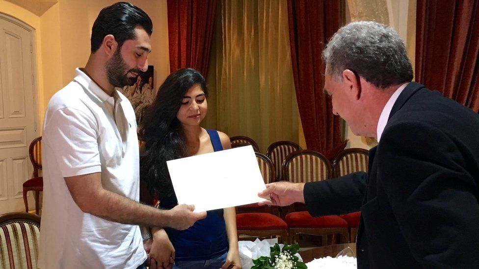 Abdul Kader and Rachelle being presented with a wedding certificate by Michaelakis Mallas, the marriage officer in Larnaca