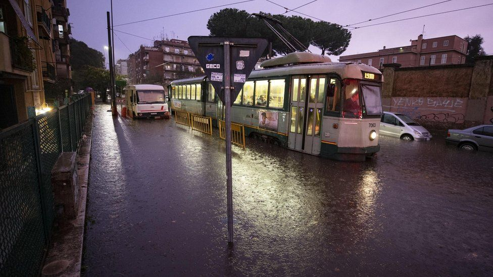 A tram drives in a flooded street due to heavy rain in Rome on 1 Nov
