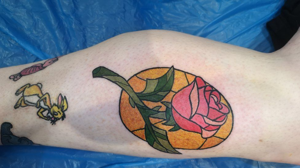 A leg with a tattoo of a rose and Disney characters