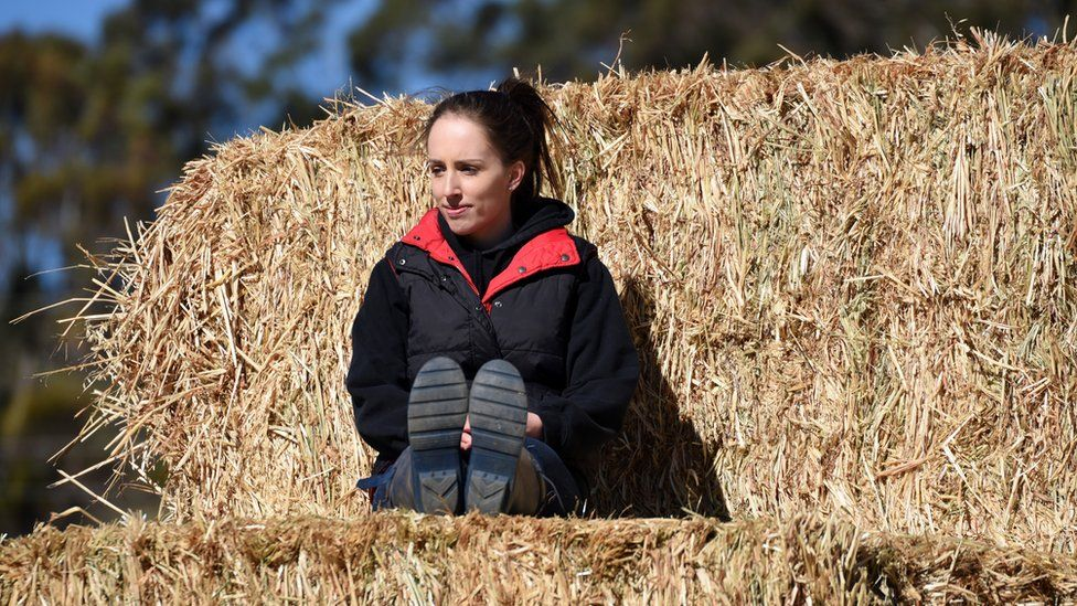 Jade Whatman sits on hay