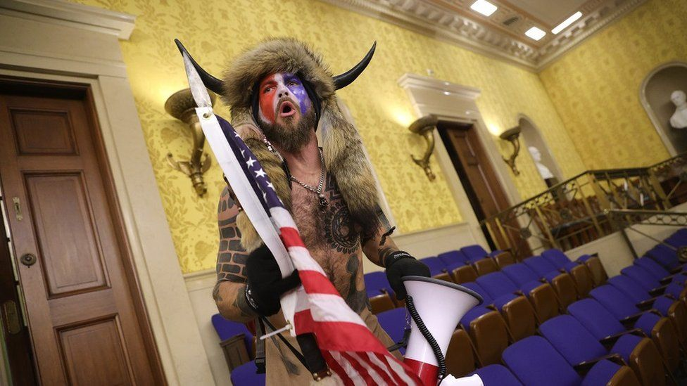 A man in horns and a fur hat, alleged to be Jake Angeli, pictured inside the Senate chamber