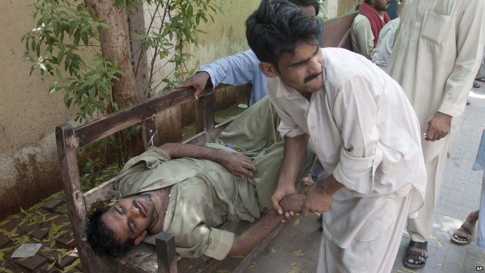 People try to help a man who fainted because of the heat in Karachi. Photo: 23 June 2015