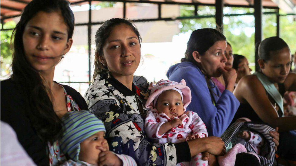 Mulheres com bebês na fila do posto de saúde