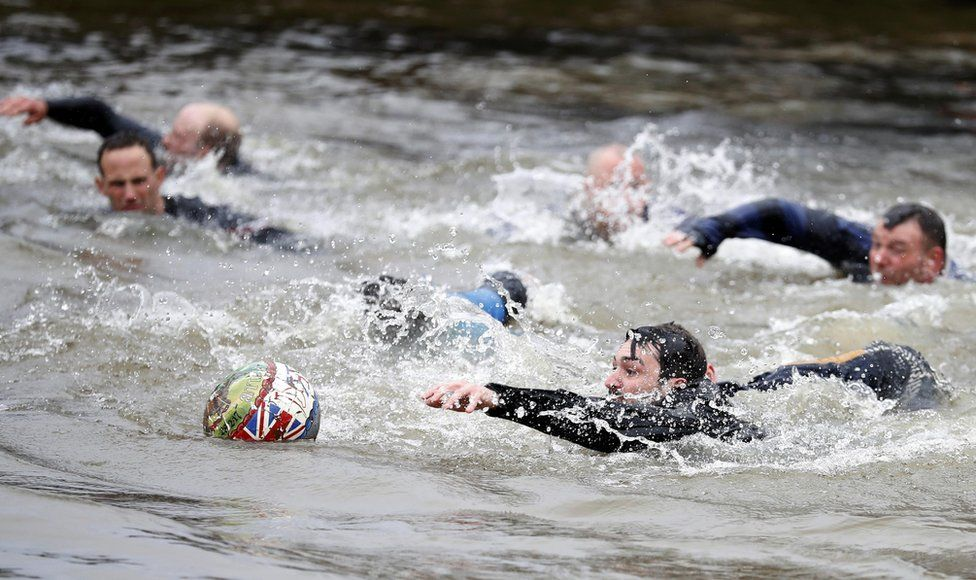 Players compete for the ball in the river during the annual Shrovetide football match in Ashbourne, 28 February 2017