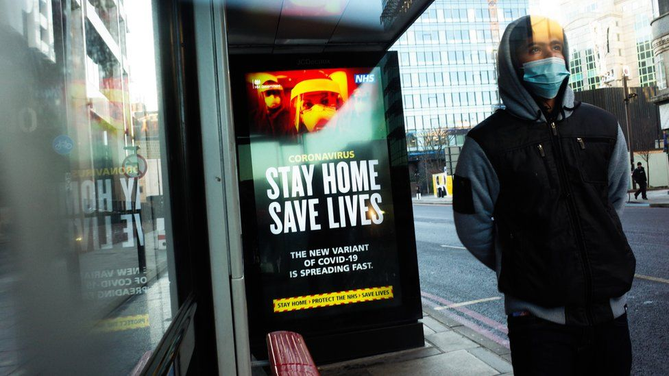 A man wears a mask at a bus stop with a Stay Home Save Lives poster