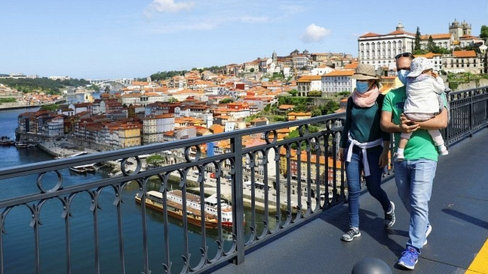 A couple wearing masks walk with their child across the Dom Luis I Bridge in Porto, Portugal
