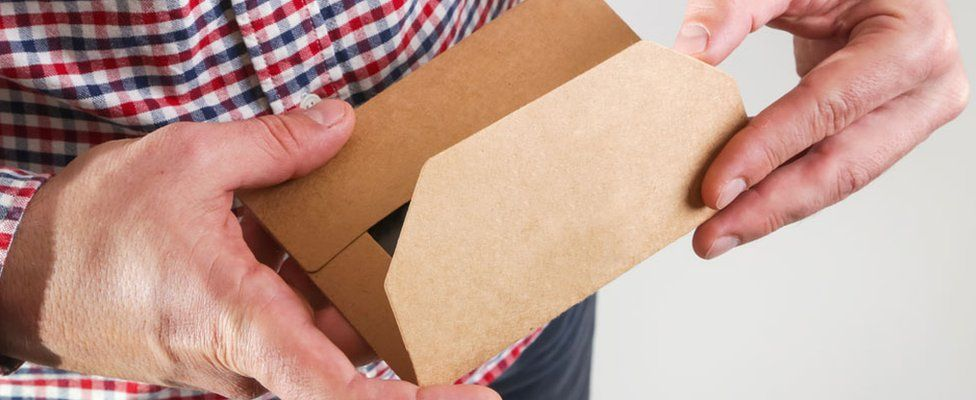 A stock picture of a man opening an envelope