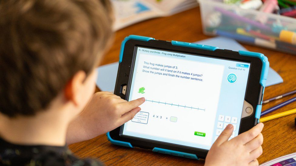 Wilfred, aged 7, does maths activities on an iPad as he takes part in home schooling at home in London