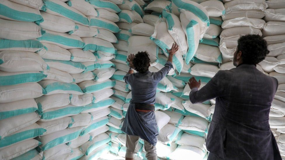 Workers handle sacks of wheat flour at a World Food Programme food aid distribution centre in Sanaa, Yemen February 11, 2020