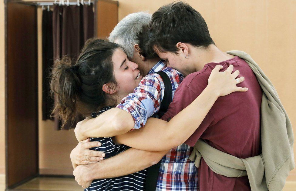 """A Catalonian familiy embraces each other after voting in the """"1-O Referendum"""" at a Sports Center in Sant Julia de Ramis, Girona,"""