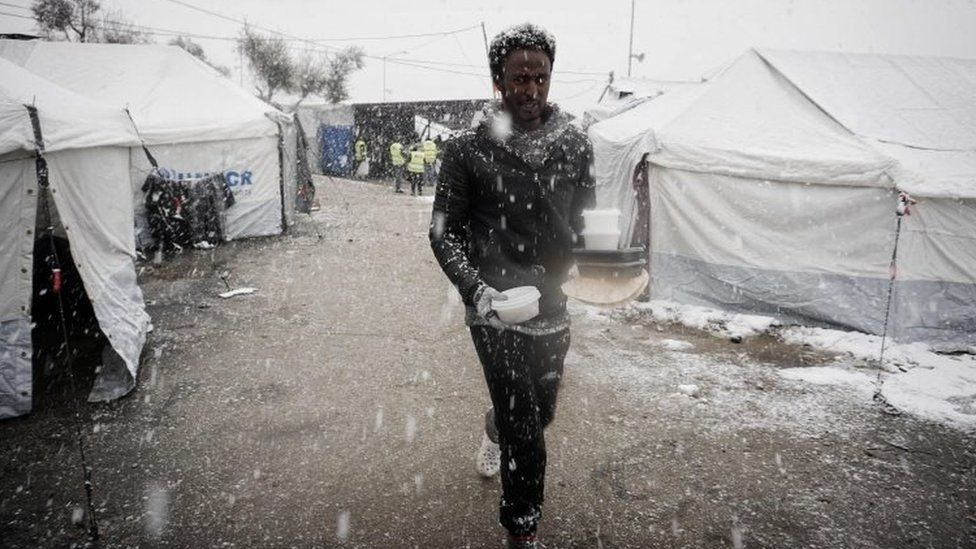 A migrant walks after receiving food in a camp on the Greek island of Lesbos. Photo: 9 January 2017