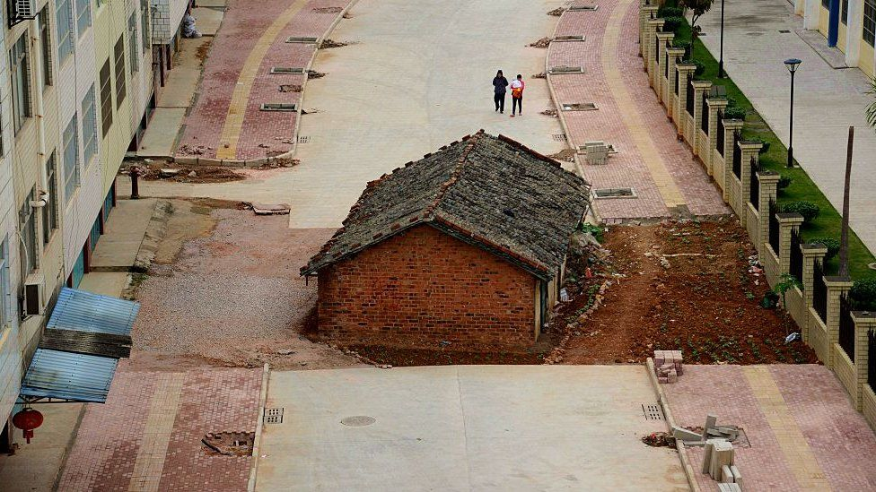 A 'nail' house blocks the road almost completely outside a residential block on April 10, 2015 in Nanning, South China.